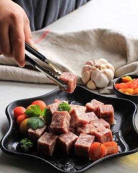 Chef feminina preparando carne premium wagyu degelada ou saikoro, carne de mármore cortada em cubos para grelha, tepanyaki ou yakiniku