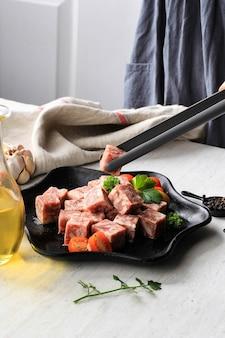 Chef feminina que prepara carne premium wagyu degelada ou saikoro, carne de mármore cortada em cubos para grelha, tepanyaki ou yakiniku. copiar espaço para texto