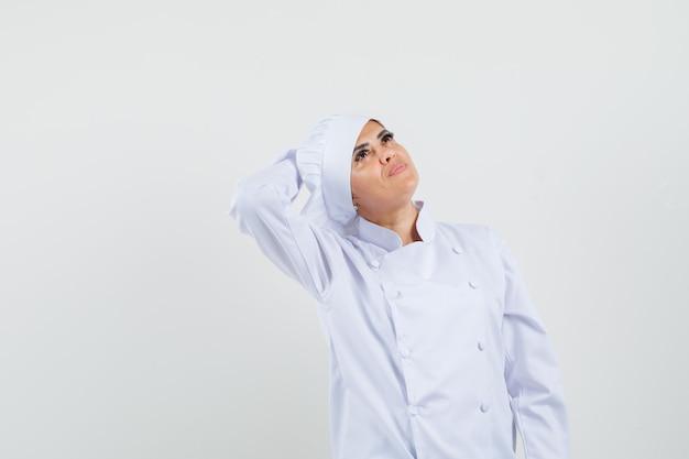 Chef feminina segurando a mão atrás da cabeça em um uniforme branco e parecendo sonhadora