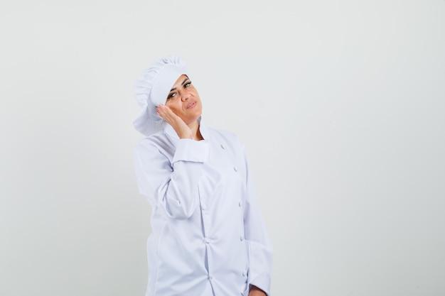 Chef feminina segurando a mão perto da bochecha com uniforme branco e parecendo confiante