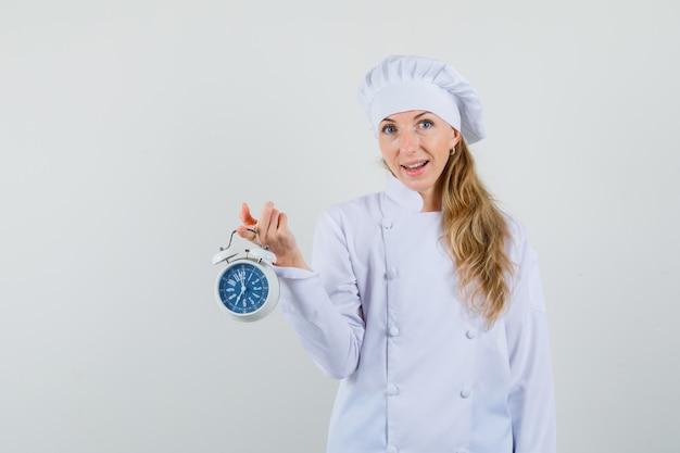 Chef feminina segurando um despertador em uniforme branco e parecendo alegre