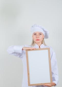 Chef feminina segurando um quadro branco em uniforme branco e olhando séria
