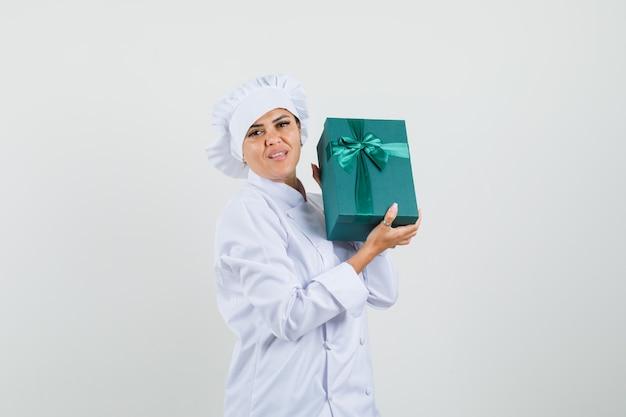 Chef feminina segurando uma caixa de presente em uniforme branco e parecendo confiante