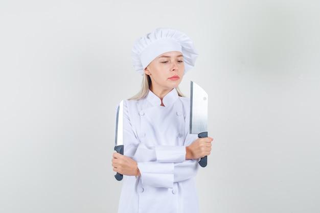 Chef feminina segurando uma faca e um cutelo de uniforme branco e olhando séria