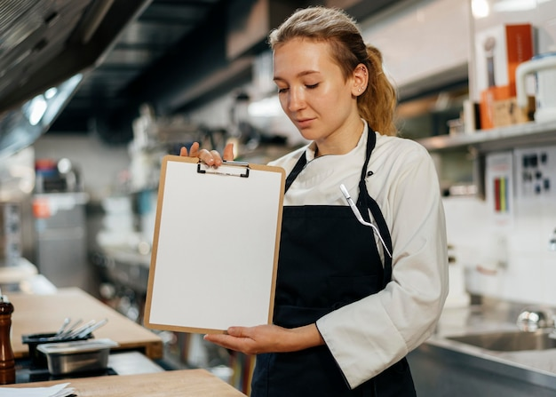 Chef feminina segurando uma prancheta na cozinha
