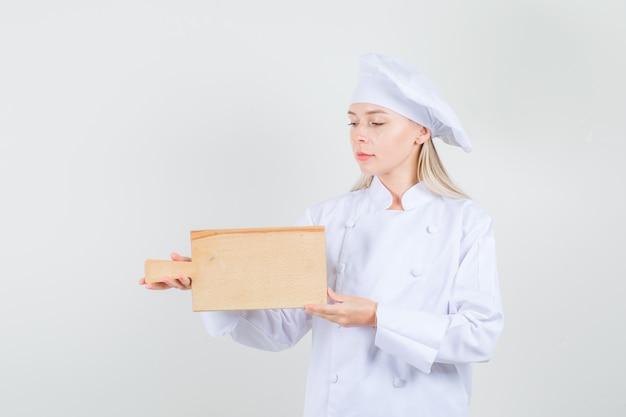 Chef feminina segurando uma tábua de corte em uniforme branco