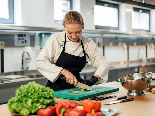 Chef feminina sorridente cortando vegetais na cozinha