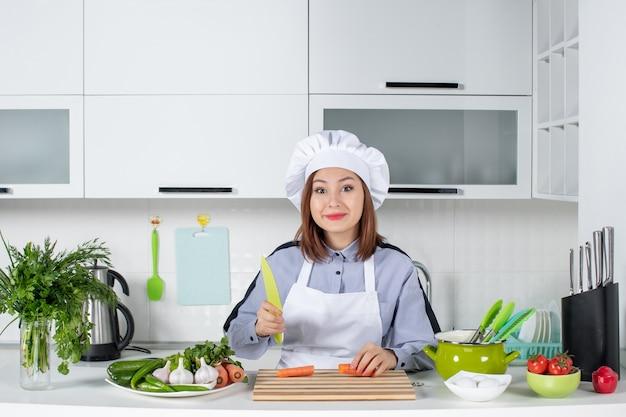 Chef feminina sorridente e vegetais frescos com equipamento de cozinha e cenoura cortada na cozinha branca
