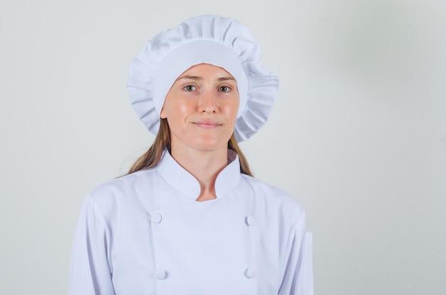 Chef feminina sorrindo e olhando para a câmera em uniforme branco