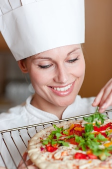 Chef feminina sorrindo preparando uma pizza