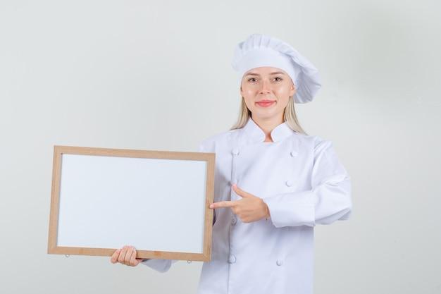 Chef feminino apontando o dedo para quadro branco em uniforme branco e olhando alegre.