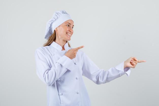 Chef feminino apontando os dedos para o lado em uniforme branco e parecendo alegre. vista frontal.