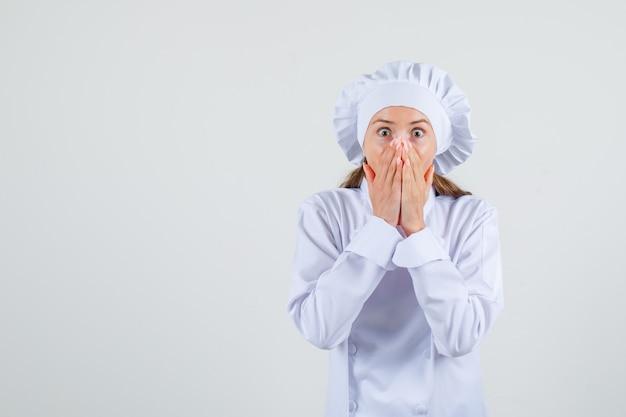 Chef feminino cobrindo a boca com as mãos em uniforme branco e parecendo assustado. vista frontal.