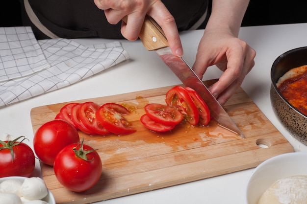 Chef feminino corta os tomates.