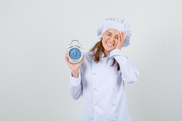 Chef feminino de uniforme branco segurando o despertador com a mão na bochecha e olhando feliz, vista frontal.