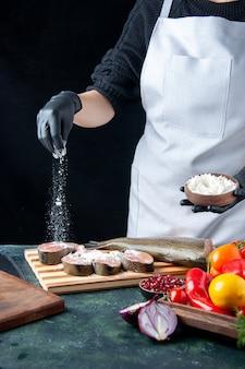 Chef feminino de vista frontal com avental cobrindo fatias de peixe cru com farinha de legumes frescos na placa de madeira faca tigela de farinha na mesa da cozinha