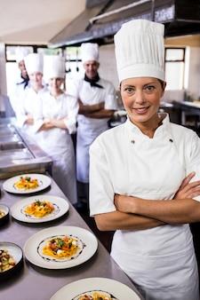 Chef feminino em pé com os braços cruzados na cozinha