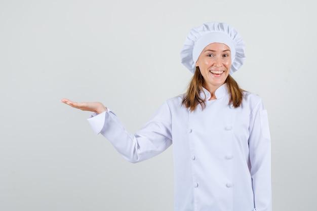 Chef feminino em uniforme branco dando boas-vindas ou mostrando algo com a palma da mão aberta e olhando feliz, vista frontal.