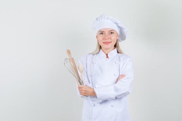 Chef feminino segurando a colher de pau, batedor, rolo de uniforme branco e olhando alegre.