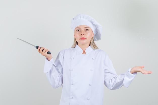 Chef feminino segurando a faca em uniforme branco e olhando sério.