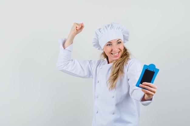 Chef feminino segurando a mini prancheta com o vencedor gesticulando para baixo em uniforme branco e parecendo feliz.