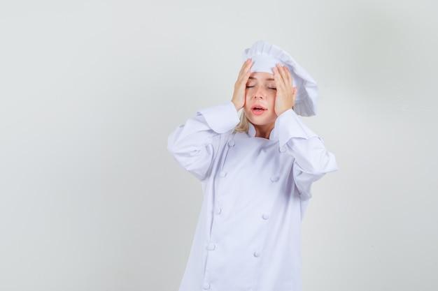 Chef feminino segurando as mãos na cabeça em um uniforme branco e parecendo arrependido.