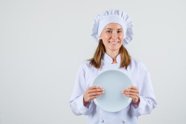 Chef feminino segurando o prato vazio em uniforme branco e parece feliz. vista frontal.