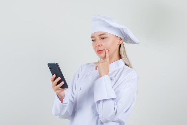 Chef feminino segurando o smartphone com o dedo na bochecha em uniforme branco.