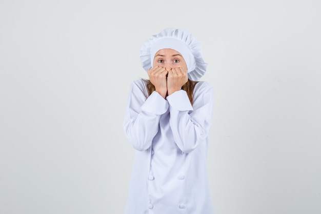 Chef feminino segurando os punhos na boca em uniforme branco e parecendo assustado. vista frontal.