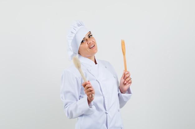 Chef feminino segurando uma colher de pau e um garfo em uniforme branco e parecendo confiante.