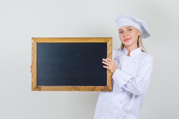 Chef feminino segurando uma lousa em uniforme branco e olhando alegre.