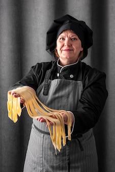 Chef feminino sorridente segurando macarrão fresco