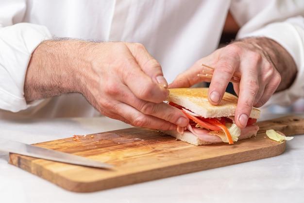 Chef finaliza sanduíche com presunto e salada