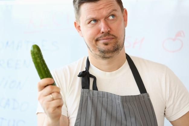 Chef frustrado segurando pepino orgânico fresco. homem de barba segura cuke verde maduro na mão.