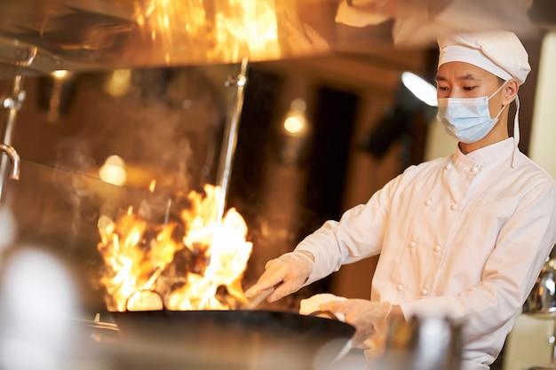 Chef habilidoso com máscara facial segurando a wok em chamas Foto Premium
