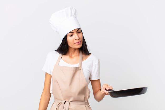 Chef hispânica segurando uma frigideira