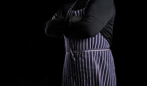 Chef homem com um avental listrado azul e roupas pretas fica de pé contra um fundo preto, com os braços cruzados sobre o peito, copie o espaço