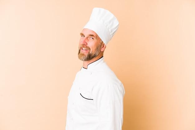 Chef homem isolado em bege parece de lado sorrindo, alegre e agradável.