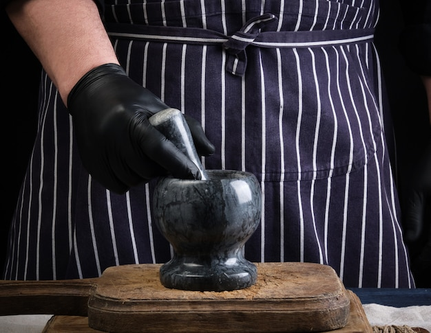 Chef homem segurando uma pedra almofariz e pilão para moer especiarias