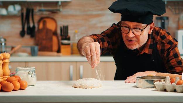 Chef idoso com bonete fazendo massa, assar biscoitos. padeiro sênior aposentado com avental, uniforme de cozinha polvilhando, peneirando e espalhando ingredientes refogados com pão e pizza caseira cozida à mão.