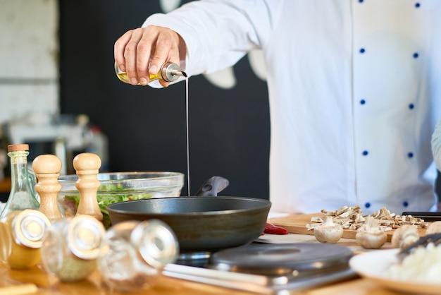 Chef irreconhecível fritar cogumelos