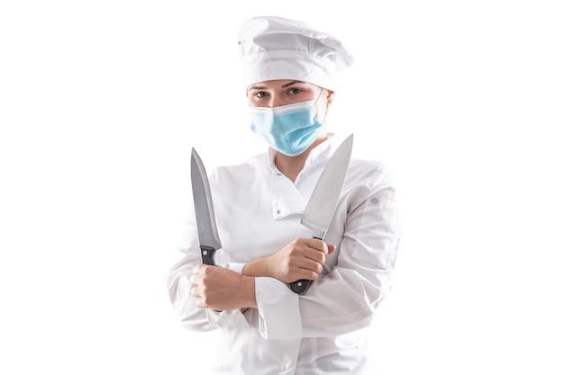 Chef isolado com máscara devido à pandemia de pé em uma túnica de cozinha branca com as mãos cruzadas, segurando duas facas afiadas.