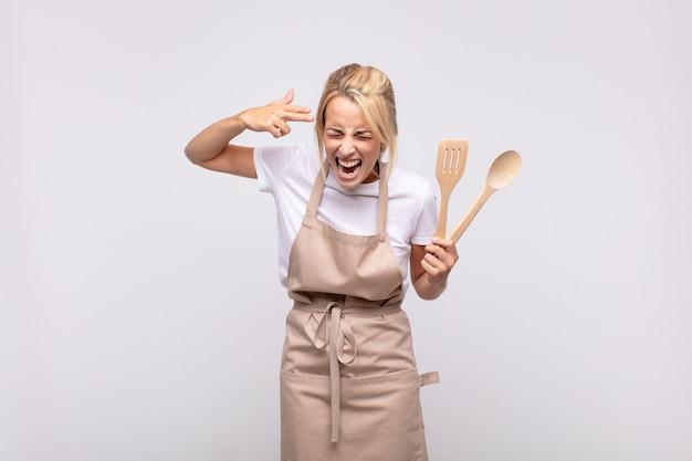Chef jovem parecendo infeliz e estressada, gesto suicida fazendo sinal de arma com a mão, apontando para a cabeça