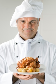 Chef maduro e orgulhoso servindo frango assado com batatas