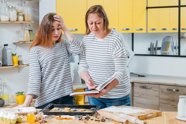 Chef mais solto. mãe segurando o livro de receitas, apontando o erro que sua filha cometeu ao cozinhar biscoitos.
