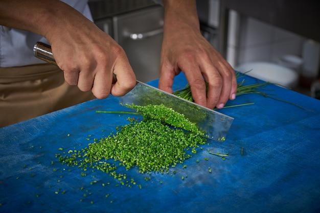 Chef mãos cebolinha de corte na cozinha do restaurante