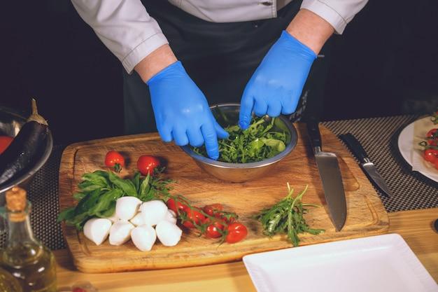 Chef mãos com luvas cozidas. o cozinheiro chefe está cozinhando um prato gourmet - mussarela com manjericão, tomates de cereja e rúcula.