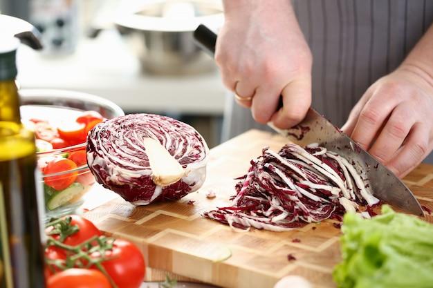 Chef mãos cortando salada roxa com repolho metade