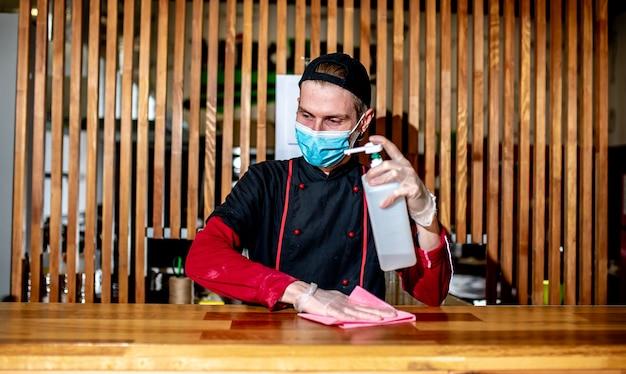 Chef mascarado desinfeta a mesa de trabalho com anti-séptico