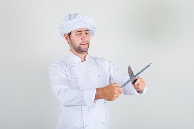 Chef masculino afiando faca em uniforme branco e parecendo ocupado